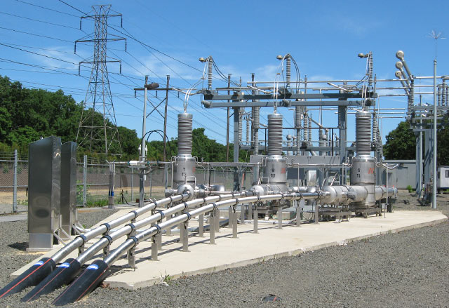 Photo shows the world's first HTS power transmission cable system installed in Long Island Power Authority's (LIPA) commercial power grid in April 2008. At full capacity, the 138 kV system is capable of carrying 574 megawatts of power and powering 300,000 homes. The three cables shown entering the ground can carry as much power as all of the overhead lines on the far left. (Courtesy of American Superconductor)